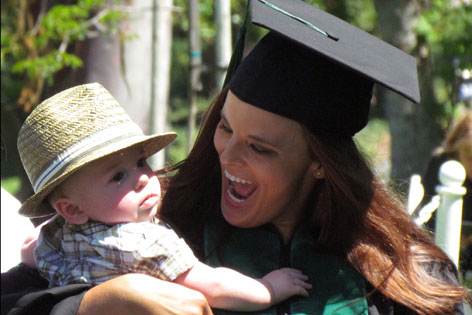 Emily Grant in cap and gown with baby